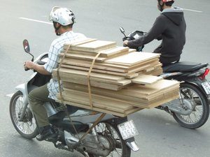 8735047-mopeds-can-do-anything-hauling-lumber-0